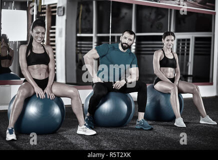 Fitness trainer with two girls posing in the gym - Stock Photo