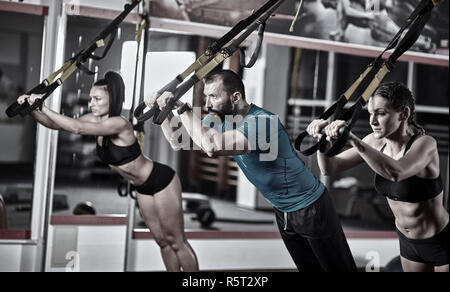 Athletic people doing crossfit training with trx straps - Stock Photo