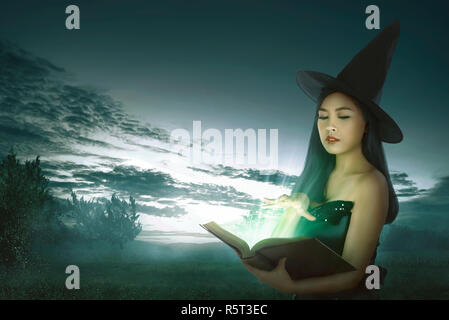 Dark asian witch woman with spell book - Stock Photo