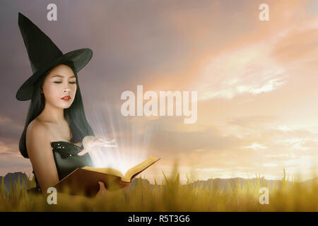 Beautiful asian witch woman with hat learning magic from the book - Stock Photo