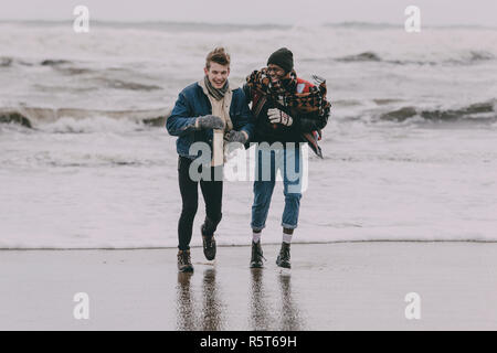 Friends Having Fun On A Winter Beach - Stock Photo