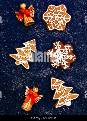Christmas cookies Top view photo Classic gingerbreads in shapes of house, spruces and snowflakes with icing are lying on dark blue desk - Stock Photo
