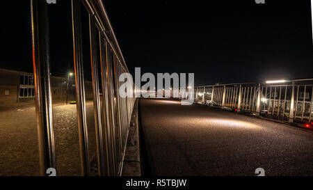 Illuminated walkway with metal silver balustrade in a curve shape. - Stock Photo