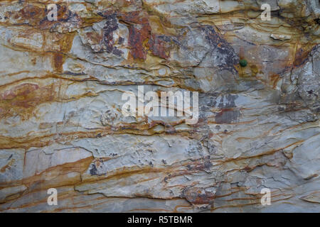 iron oxide or mineral staining on a mudstone or shale cliff southern irish coast, sandy cove, castlehaven, west cork, ireland. - Stock Photo