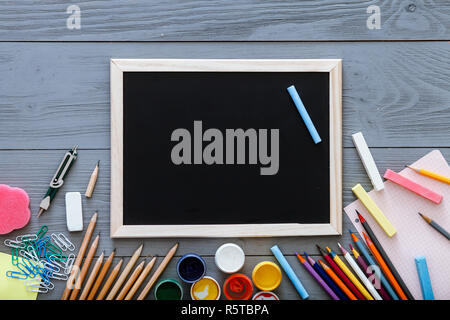 Chalkboard on grey dark desk with colorful pencils, paints, other school supplies for schoolwork, back to school sale concept, creative workplace for  - Stock Photo