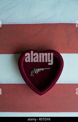 A mini silver gun in a heart shaped box against an American flag. - Stock Photo