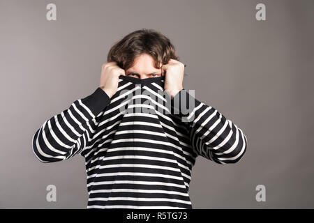 Portrait of young man with dark curly hair pulling her sweater over head having problems. Male trying disappearing in her clothes looking from underne - Stock Photo