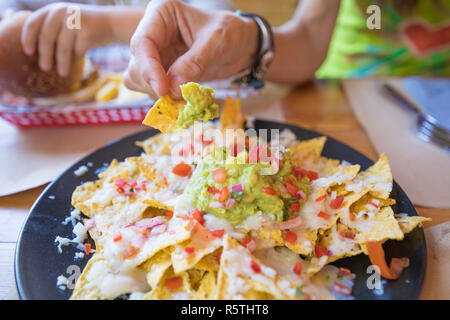 woman hand dipping nacho chips in avocado guacamole, cheese and chopped tomato on black plate, on wooden table with paper placemats at restaurant - Stock Photo
