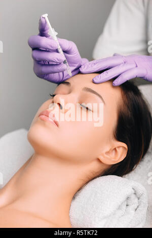 woman having facial injections for facelift and anti-aging effect, wrinkle forehead - Stock Photo