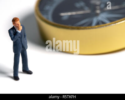 miniature figure businessman in dark blue suit standing on the side of golden compass. Concept for finding the way how to success of business