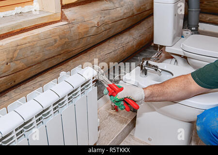 Repair of premises, valve replacement on the battery. Plumbing close-up, manual faucet crimper. - Stock Photo
