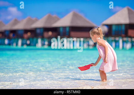 Adorable little girl playing with origami boat in turquoise sea - Stock Photo