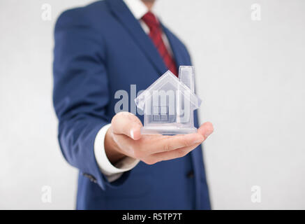 Businessman with crystal house in hand - Stock Photo