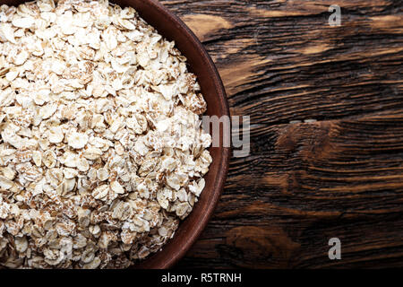 Raw oatmeal flakes in a clay plate on wooden background. healthy carbohydrate breakfast. space for text - Stock Photo