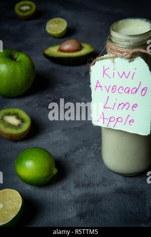 Detox green smoothie in a bottle, homemade, from blended fresh fruits like avocado, lime, kiwi, green apple and yogurt - Stock Photo