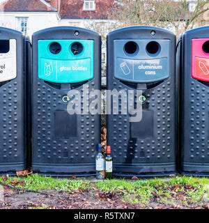 Two empty wine bottles stood in front of recycling bins - Stock Photo