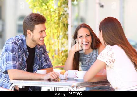Three happy friends talking sitting in a coffee shop - Stock Photo