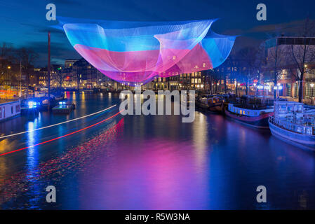Amsterdam illuminated in winter time during Amsterdam Light Festival with light trails of passing round trip boat. - Stock Photo