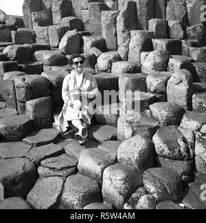 1950s, historical, a lady sitting on the ancient volcanic basalt columns at the Giant's Causeway in Co. Antrim, Northern Ireland. At the North Atlantic coast, the causeway is a geological wonder, an area of 40,000 interlocking basalt stone columns, the result of an ancient volcanic fissure eruption. - Stock Photo