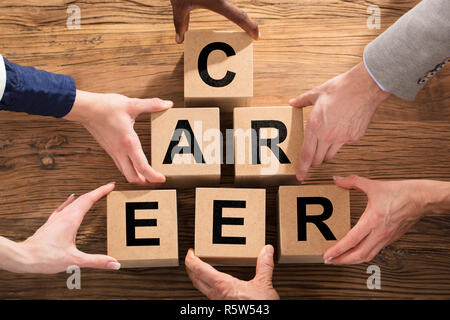 People Arranging Block On Pyramid - Stock Photo