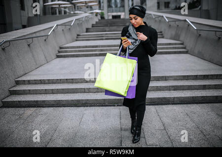 Young arabian woman walks and look at phone. She holds shopping bags. Model touches edge of her hijab - Stock Photo