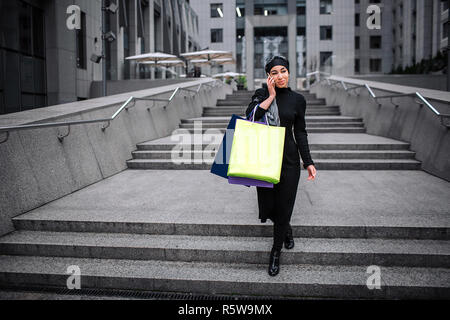 Beautiful arabian model walks on steps and look on right. She talks on phone and care shopping bags. Young woman wears hijab - Stock Photo