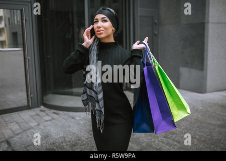 Modern and fashioned young arabian woman walks and talks on phone. She cary shopping bags behind shoulder - Stock Photo