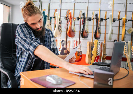 Young bearded guy sit at table and work in room. He talks on phone and hold hand on laptop keyboard. Also young man has document in hand. Guy is busy. - Stock Photo