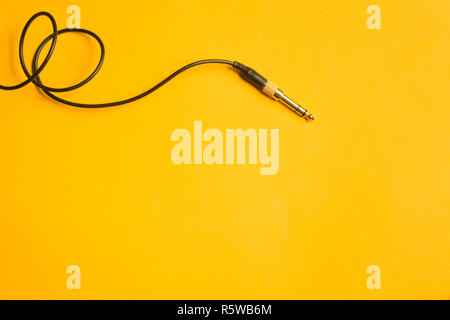 Audio jack with black cable isolated on yellow - Stock Photo