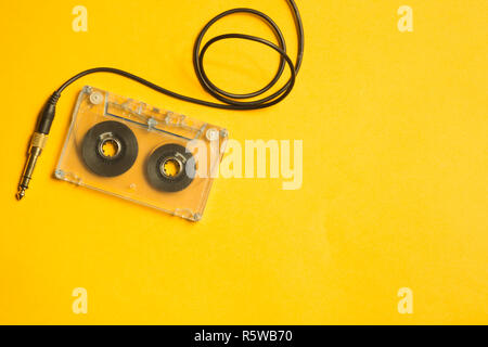 Retro cassette tape and audio jack on the yellow background - Stock Photo