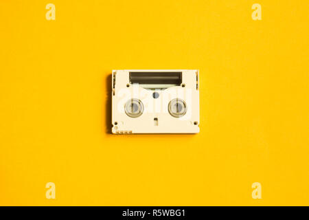 Digital video cassette on yellow background - Stock Photo