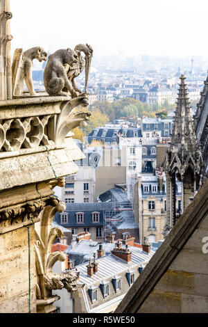 Three stone statues of chimeras overlooking the rooftops of the historic center of Paris from the towers gallery of Notre-Dame cathedral with the city - Stock Photo