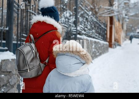 Two girls walking along the winter snowy street of the city, children are holding hands, back view. - Stock Photo