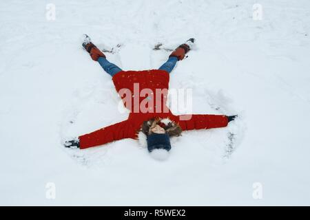 Winter portrait of cheerful girl having fun in the snow, lying on the snow in the form of angel, top view. - Stock Photo