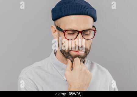 Headshot of sad lonely serious male keeps hand under chin, has dark bristle, looks down, thinks about promotion and starting new career, wears spectac - Stock Photo