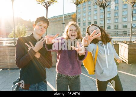 Portrait of friends teen boy and two girls smiling, making funny faces, showing victory sign in the street. City background, golden hour. - Stock Photo