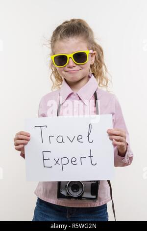 Little tourist specialist, child girl with a photo camera in sunglasses holding white sheet of paper with the text Travel expert, white background. - Stock Photo