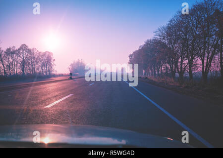 View from windscreen. Beautiful sunrise over road in autumn - Stock Photo