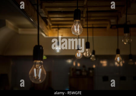 Vintage incandescence lightbulbs, with their iconic filament, hanging on the roof inside a hipsterish industrial room  Picture of lightbulbs hnging fr - Stock Photo