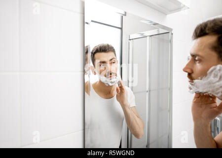 Handsome man in white t-shirt shawing his beard with blade and foam in the bathroom