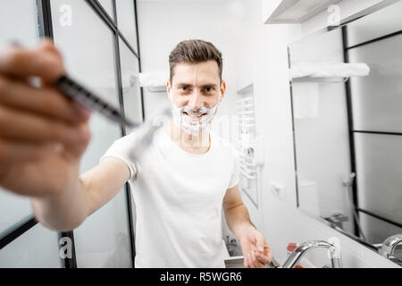 Portrait of a playful man in white t-shirt shawing with blade and foam in the bathroom
