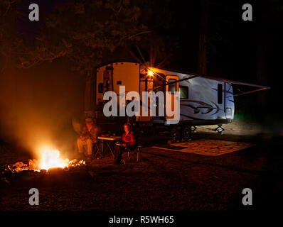 42,887.03156 man woman couple dry camping quietly thoughtfully watching roaring campfire at night by a cozy RV travel trailer - Stock Photo