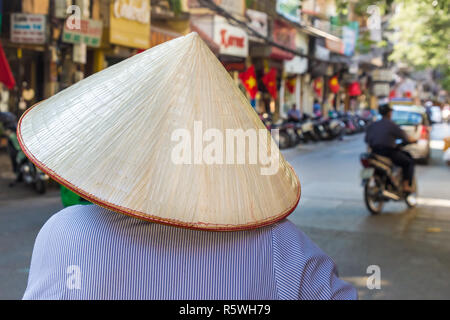 unrecognizable female in traditinal asian hat on the street of Hanoi, Vietnam - Stock Photo