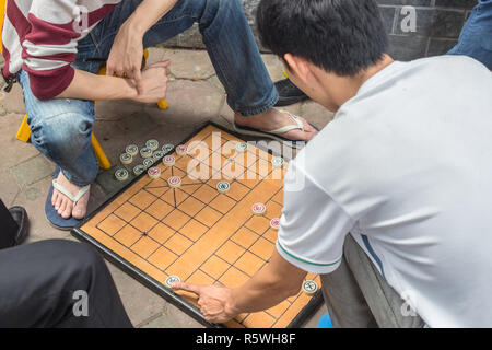 2 men, on the street in Hanoi, Vietnam, play Xiangqi, popular in Asia board game, known also as chinese chess. - Stock Photo