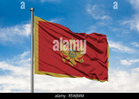 Flag of Montenegro waving in the wind against white cloudy blue sky. Montenegrin flag. - Stock Photo