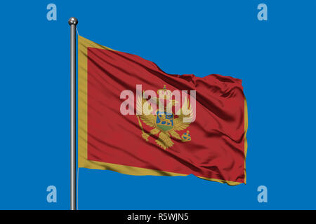 Flag of Montenegro waving in the wind against deep blue sky. - Stock Photo
