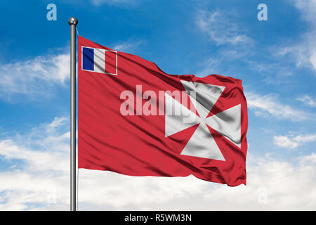 Flag of Wallis and Futuna waving in the wind against white cloudy blue sky. - Stock Photo