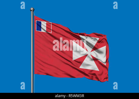 Flag of Wallis and Futuna waving in the wind against deep blue sky. - Stock Photo