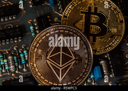 bitcoin and ethereum coin on circuit board - Stock Photo