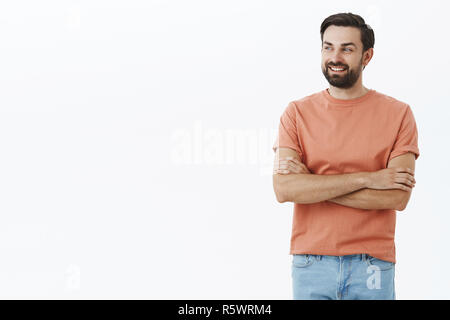 Father looking at son playing on playground feeling proud and happy. Charming adult bearded male with black hair crossing arms on chest in confident a - Stock Photo